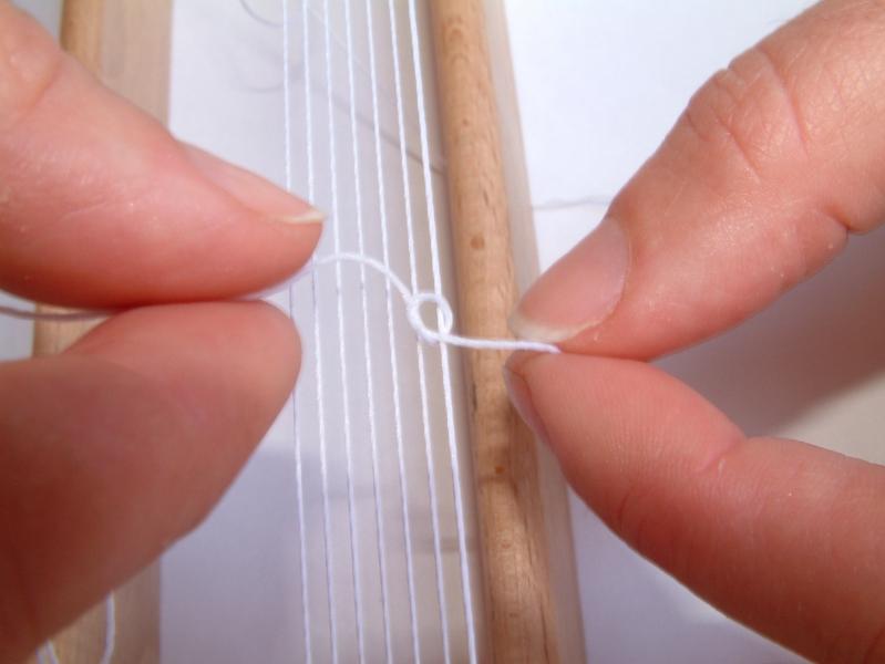 1) Připravte si osnovu; v tomto případě je složena ze 7 napnutých bavlnek. Další bavlnku provlékněte uchem jehly a volný konec uvažte na krajní nitku osnovy