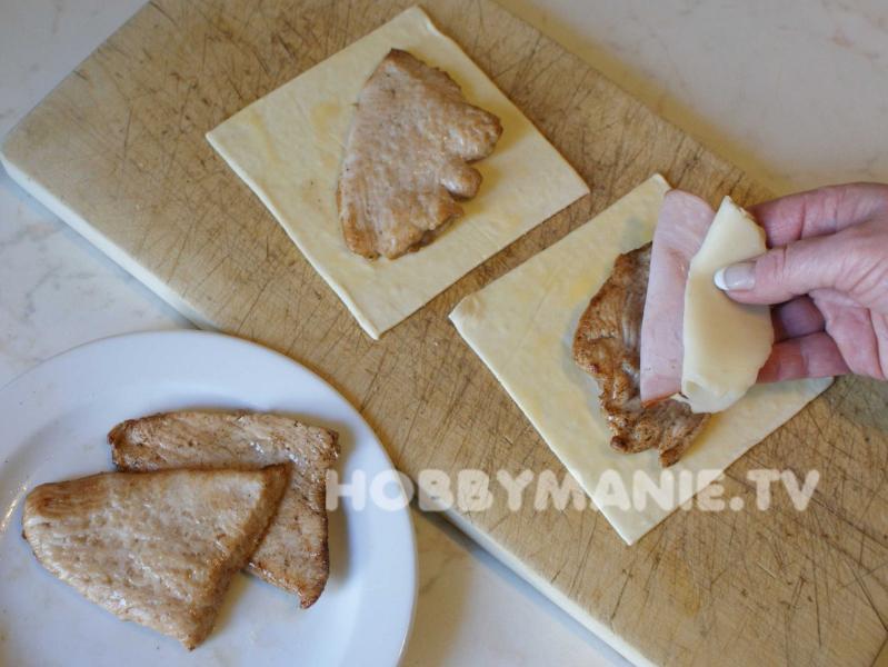 3. Na takto upravené plátky těsta (ještě ne zcela rozmrzlé) položte po krůtím filetu a navrch přidejte plátek šunky a tvrdého sýra